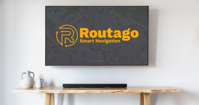Routago logo on a TV-screen mounted on the wall. Below a shelf with a soundbar and two white vases